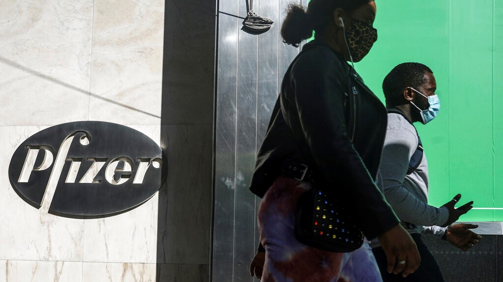 In this Nov. 9, 2020, file photo, pedestrians walk past Pfizer world headquarters in New York.(AP Photo/Bebeto Matthews, File)