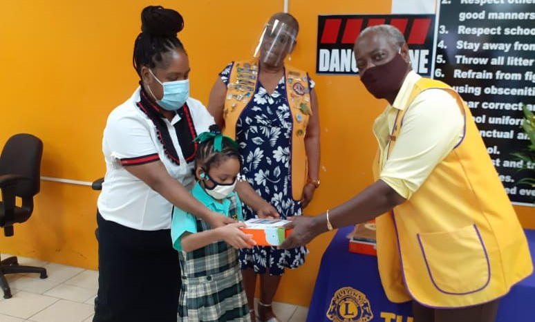 A member of the Tunapuna Lions Club hands over a device to a young student and parent.
