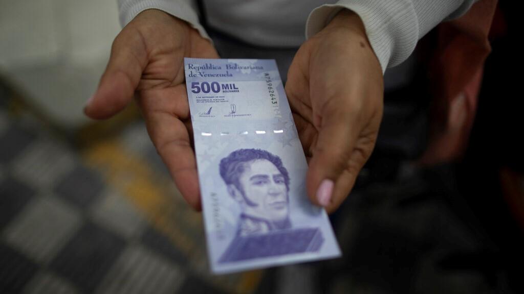 档案-在这张2021年3月16日的资料照片中,一名女子从委内瑞拉加拉加斯的一家银行取出一张新的50万玻利瓦尔纸币。(美联社照片/阿里安娜·库比洛斯,档案)