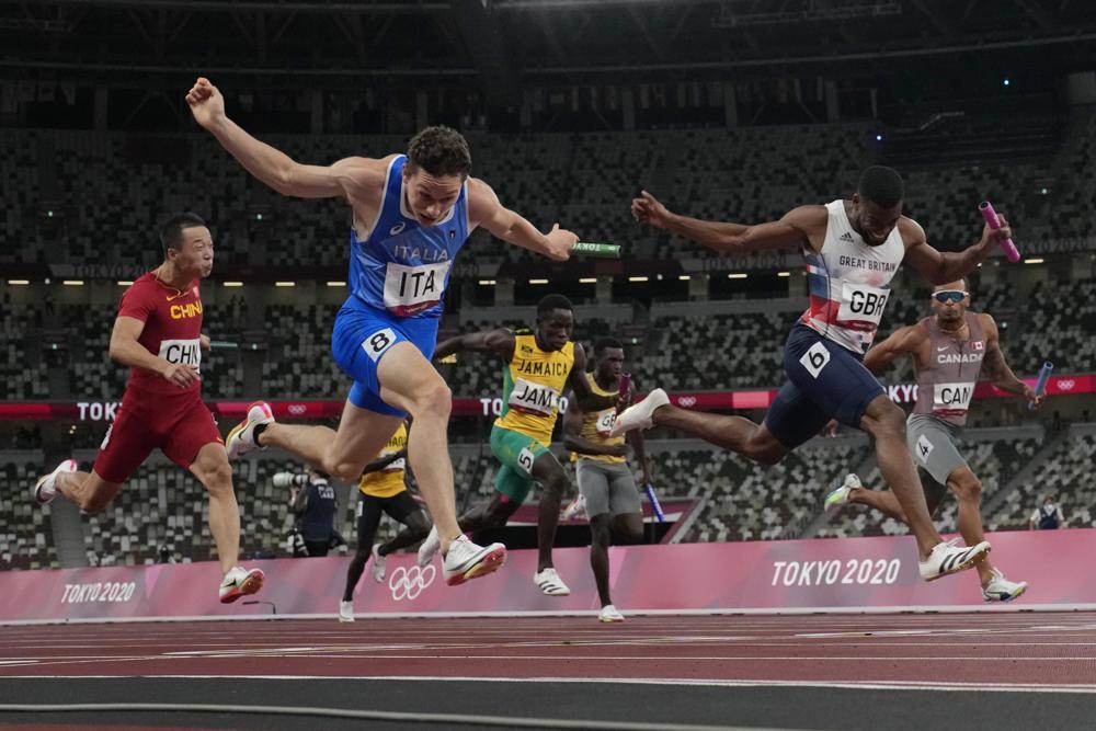 2020年8月6日,在东京举行的2020年夏季奥运会男子4x100米接力赛中,意大利选手菲利浦·托尔图领先英国选手纳撒尼尔·米切尔-布莱克,为自己的团队赢得了一枚金牌。(美联社图片/大卫·j·菲利普)