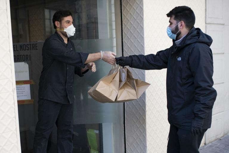 Un livreur de Delivery4Heroes vient récupérer des repas pour les soignants qui combattent le coronavirus, dans un restaurant de Barcelone le 4 avril 2020 (AFP - Josep LAGO)