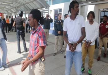 Accused scammers being escorted by US marshalls from a police post at the Norman Manley International Airport on Wednesday morning.