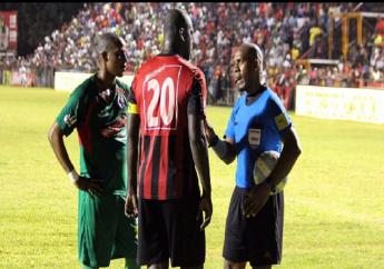 FIFA referee Karl Tyrell (right) warns Arnett Garden's captain O'Neil Thompson (#20) and midfielder Woolery Woolfe after they were involved in a physical confrontation during their first-leg semi-final match of the Wray and Nephew National Premier League earlier this month.