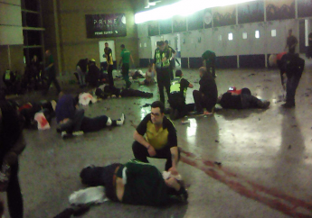 Helpers attend to injured people inside the Manchester Arena, Manchester, Britain, after a blast Monday, May 22, 2017. (PA via AP)