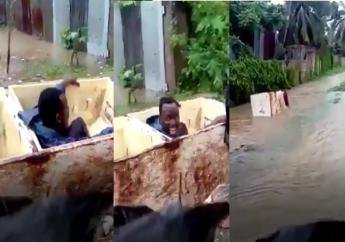 A man has a 'blast' using an old refrigerator as a makeshift boat in flood waters.