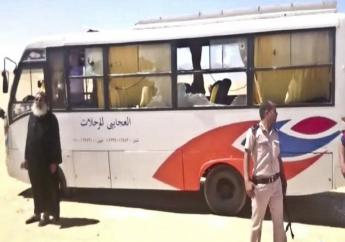 This image released by the Minya governorate media office shows a policeman and a priest next to a bus after gunmen stormed the bus in Minya, Egypt, Friday, May 26, 2017. Egyptian officials say dozens of people were killed and wounded in an attack by masked militants on a bus carrying Coptic Christians, including children, south of Cairo.