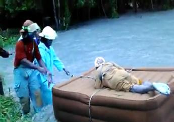 In this screen shot of a video shared on Facebook, an elderly woman is shown being rescued by Jamaica Fire Brigade personnel during floods in Linstead, St Catherine on Tuesday.