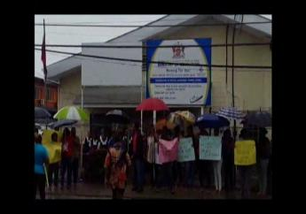 In this June 2016 photo, parents are seen braving heavy rains to protest over stoppage of work on the Preysal Government Primary School