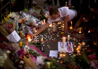 A man lights candles after a vigil in Albert Square, Manchester, England, Tuesday May 23, 2017, the day after the suicide attack at an Ariana Grande concert that left 22 people dead as it ended on Monday night. (AP Photo/Emilio Morenatti)