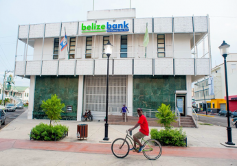 A cyclist rides past Belize Bank in downtown Belize City, April 23, 2017. Photo courtesy Caribbean Network Operators Group.