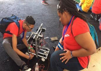 Twee van de drie teamleden bezig met 'Sweef Teki', hun zelfgebouwde robot. Foto: Young Help Suriname