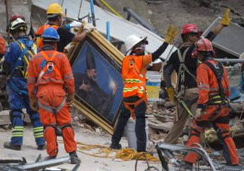 Search and rescue workers remove a painting from a felled office building brought down by a 7.1-magnitude earthquake, as others raise their arms as a sign for people to maintain silence during their search for survivors in the Roma Norte neighborhood of Mexico City, Saturday, Sept. 23, 2017. (AP Photo/Moises Castillo)