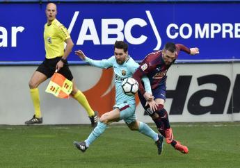 Barcelona's Lionel Messi, battles for the ball with Eibar's Anaitz Arbilla during their Spanish La Liga football match  at Ipurua stadium, in Eibar, northern Spain, Saturday, Feb.17, 2018.