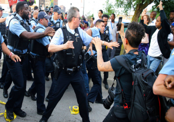 Members of the Chicago police department scuffle with an angry crowd at the scene of a police involved shooting in Chicago, on Saturday, July 14, 2018. (Nuccio DiNuzzo/Chicago Tribune via AP)