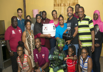 Machel Montano or Machel Montano Foundation for Greatness presenting Siparia community chocolate making group with equipment to start their training.