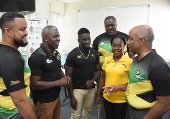 Christopher Samuda (right), president of the Jamaica Olympic Association (JOA) and Ryan Foster (left), JOA CEO greet some members of Jamaica's delegation during the official send-off of the men's and women's rugby teams to the Pan Am Games qualifiers in Barbados.  The occasion took place at the JOA headquarters in Kingston on Tuesday.