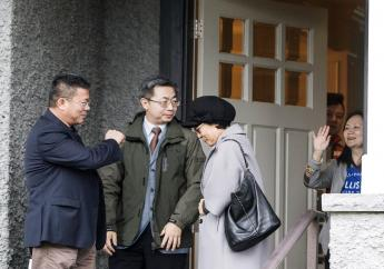 Huawei chief financial officer Meng Wanzhou, right, waves goodbye to visitors at her home in Vancouver on Wednesday, Dec. 12, 2018. (Jonathan Hayward/The Canadian Press via AP)