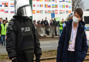 A climate conference participant looks at a police officer during the March for Climate, a protest against global warming in Katowice, Poland, Saturday, Dec. 8, 2018, as the COP24 UN Climate Change Conference takes place in the city. (AP Photo/Alik Keplicz)
