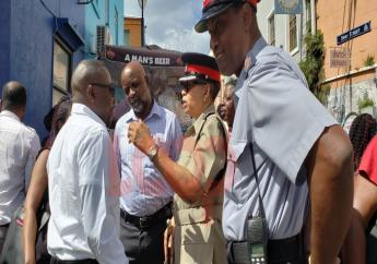 Minister Dwight Sutherland chatting with members of the Royal Barbados Police Force prior to commencing his Swan Street tour.