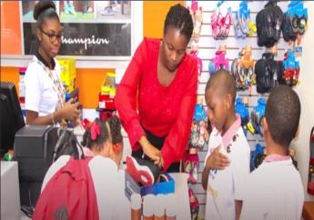 Payless attendant assisting children from Variety the Childrens Charity as part of the Christmas giveback in Barbados. (FILE)