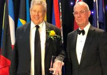 """The Hon. Gordon """"Butch"""" Stewart, Chairman and Founder, Sandals Resorts (left) accepts the 2019 Chancellor's Award fromRobert Bermudez, Chancellor of the University of West Indies."""