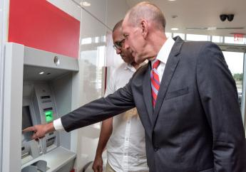 David Parks - Managing Director, Caribbean East, Scotiabank assists customer, Roger Thomas as he used one of the newly installed next generation ATMs - Intelligent Deposit Machines (IDMs) at the Warrens branch.