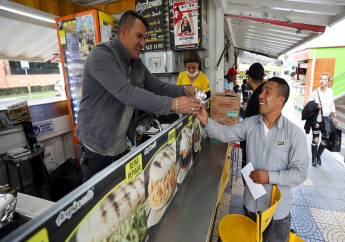 """In this June 11, 2019 photo, Gerson Briceno, owner of the fast food restaurant """"Arepas Cafe"""" serves a customer in Bogota, Colombia, Tuesday, June 11, 2019. Today, Arepas Café has nine locations around Bogotá. """"I always missed the flavor of home,"""" he said. (AP Photo/Fernando Vergara)"""