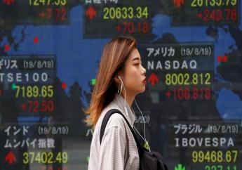 A woman walks by an electronic stock board of a securities firm in Tokyo, Tuesday, Aug. 20, 2019.  (AP Photo/Koji Sasahara)