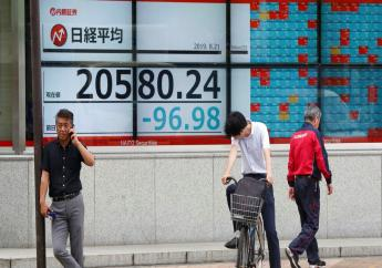 People stand by an electronic stock board of a securities firm in Tokyo, Wednesday, Aug. 21, 2019.  (AP Photo/Koji Sasahara)