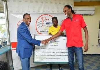 Jamaica Cricket Association (JCA) President Wilford Heaven (left) and Maurice Broadbell, Operations Supervisor at Pace Electrical Works, shake hands following the presentation of a symbolic cheque for the women's cricket programme. Occasion was a press conference to announce Pace Electrical Works as a sponsor of the national women's cricket programme at Sabina Park on Wednesday, February 19. Sharing in the moment is young star Rashada Williams.
