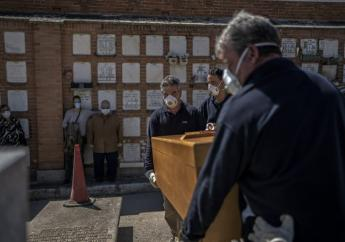 The daughter and husband of an elderly victim of the COVID-19 stand as undertakers place the coffin in the grave at the Almudena cemetery in Madrid, Spain. (AP Photo/Olmo Calvo)