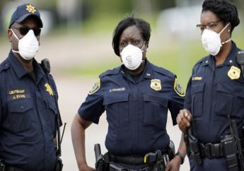 Law enforcement officers wear masks while working at a newly opened free drive through Covid-19 testing site provided by United Memorial Medical Center Thursday, April 2, 2020, in Houston. The new coronavirus causes mild or moderate symptoms for most people, but for some, especially older adults and people with existing health problems, it can cause more severe illness or death. (AP Photo/David J. Phillip)