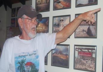 David Lea, owner of Hilltop Coffee House going through some of the photographs on the wall of his mini museum. Photo: Laura Dowrich-Phillips