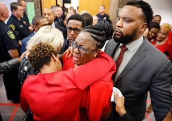 Botham Jean's mother, Allison Jean, center, escorted by civil rights attorney Lee Merritt, right,, is hugged by family members outside the courtroom after fired Dallas police officer Amber Guyger was found guilty of murder, Tuesday, Oct. 1, 2019, in Dallas. (Tom Fox/The Dallas Morning News via AP, Pool)