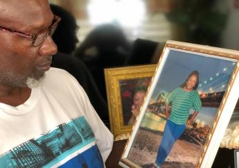 Dave Sinclair looking at a photo of his wife who died under undetermined circumstances at the National Chest Hospital in St Andrew on Wednesday.