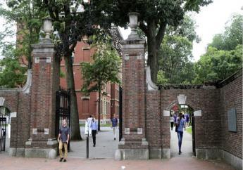 FILE - In this Aug. 13, 2019, file photo, pedestrians walk through the gates of Harvard Yard at Harvard University in Cambridge, Massachusetts. (AP Photo/Charles Krupa, File)