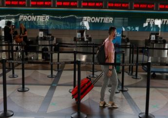 (FILE) A lone traveler heads to the ticketing counter of Frontier Airlines in the main terminal of Denver International Airport on July 22, 2020, in Denver. Hotel and home-sharing reservation site Booking.com plans to lay off 25% of its workforce, or more than 4,000 people, due to the impact of the new coronavirus on travel. Connecticut-based parent company Booking Holdings said Tuesday, Aug. 4, that the layoffs will begin next month. (AP Photo/David Zalubowski, File)