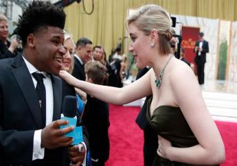 """In this February 9, 2020 file photo, Greta Gerwig, right, talks to Jerry Harris on the red carpet at the Oscars at the Dolby Theatre in Los Angeles. Harris, the star of the Netflix documentary series """"Cheer,"""" was arrested Thursday, Sept. 17 on child pornography charges. (AP Photo/John Locher File)"""
