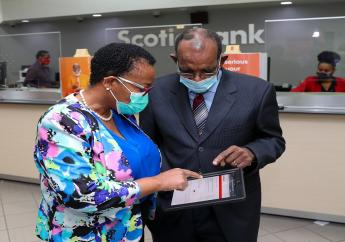 Seniors like Percival Latouche ( right), President of the Jamaica Association for Resettlement of Returning Residents are being encouraged to use Scotiabank's digital channels . Here Latouche is assisted by Pamela Douglas ( left) , Manager of the Scotiabank New Kingston branch to use the new Scotiabank mobile app.