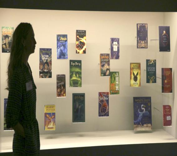 "A member of British Library staff poses for a picture with Harry Potter books published in several languages at the ""Harry Potter - A History of Magic"" exhibition at the British Library, in London, Wednesday Oct. 18, 2017."