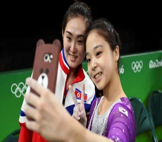 Een Noord- en een Zuid-Koreaanse atleet maken een selfie op de Rio 2016 Olympische Spelen. Foto: Reuters