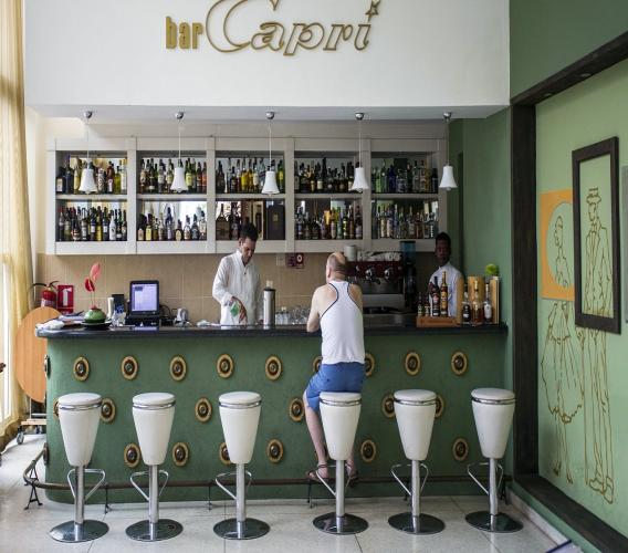 (Image: AP: A customer sits at the bar of the Hotel Capri in Havana on 12 September 2017)