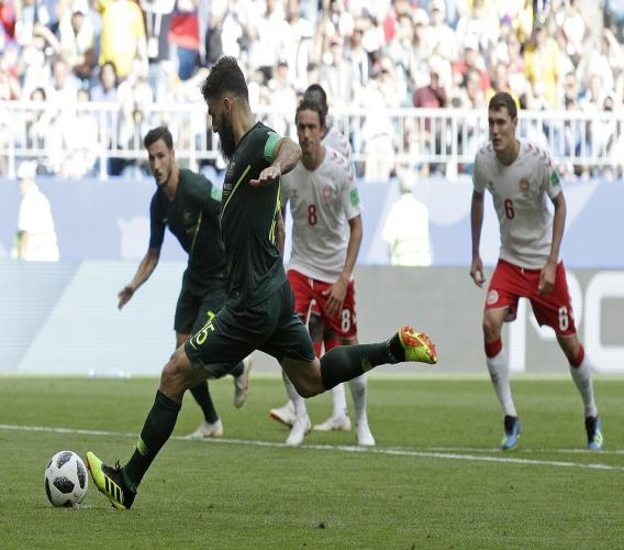 Australia's Mile Jedinak scores  from the penalty spot during the group C match against Denmark at the 2018 football World Cup in the Samara Arena in Samara, Russia, Thursday, June 21, 2018. (AP Photo/Gregorio Borgia).