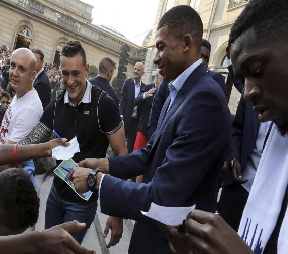 France forward Kylian Mbappe, centre, and forward Ousmane Dembele sign autographs during an official reception at the Elysee Presidential Palace in Paris, Monday. (Ludovic Marin/Pool Photo via AP)
