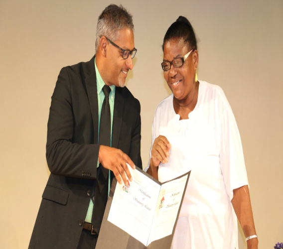 Senator the Honourable Clarence Rambharat, Minister of Agriculture, Land and Fisheries (left), shares a light moment with a recipient during a Statutory Lease Distribution Ceremony hosted by the Land Settlement Agency (LSA) at the Government Campus Plaza in Port of Spain on Friday 20th July, 2018 (Photo: Ministry of Agriculture, Land and Fisheries)