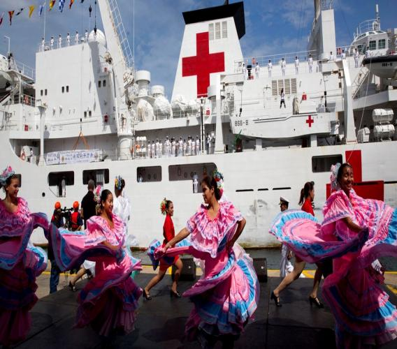"""Venezuelan dancers welcome the arrival of Chinese navy hospital ship """"The Peace Ark"""" docked at the port in la Guaira, Venezuela, Saturday, Sept. 22, 2018. (AP Photo/Ariana Cubillos)"""