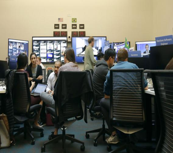 Workers gather and sit and their desks during a demonstration in the war room, where Facebook monitors election related content on the platform, in Menlo Park, California (AP Photo/Jeff Chiu)