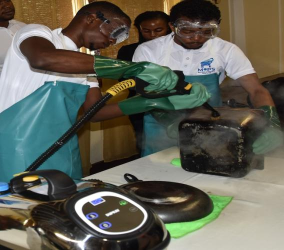 Technicians from Masters Of Property Sanitation (MOPS), Ijahneil Wilkins (left) and Raheem Williamson (right) demonstrate cleaning of a restaurant item, sanitizing and removing stains with MOPS' High Pressurized Steam Cleaning Unit.