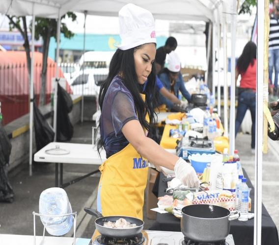 'Bad Gyal' Ce'Cile whips up her shrimp pasta during the SunCity Bubble Di Pot For Charity Cook-Off at Mandela Park in Half-Way Tree recently. (PHOTOS: Marlon Reid)