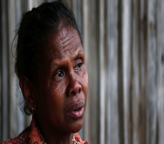 In this Oct. 21, 2018, photo, Yohanna Banunaek, cries as she talks about her late daughter Adelina Sau, in Abi village in West Timor, Indonesia. Sau had been working as a maid for a Malaysian family when a local lawmaker's office received a tip from neighbors who suspected she was being abused.